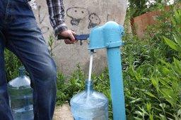 Cотрудники компании по доставке воды Серебряный родник набирают воду на колонке
